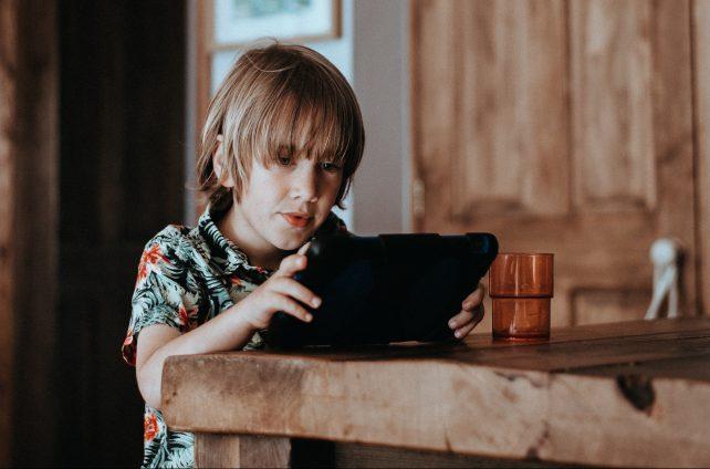 Jongen op iPad en hoort niets om zich heen