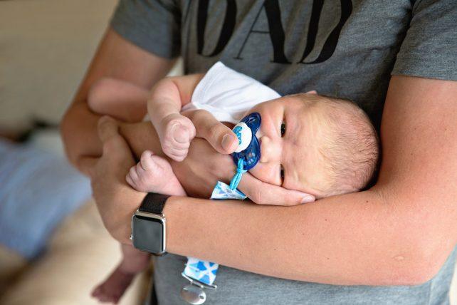partner met pasgeboren baby in zijn arm